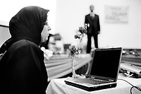 Iraq. Baghdad. Al Alweya Club. National council for women. Women conference on women issues. A secretary and her laptop computer. The woman wears the abaya and the hijab (islamic headscarf) on her head to cover her hair. The abaya, sometimes also called aba, is a simple, loose over-garment, essentially a robe-like dress, worn by some women in parts of the Islamic world. Traditional abaya are black and may be either a large square of fabric draped from the shoulders or head or a long caftan. The abaya covers the whole body except the face, feet, and hands.  The word hijab (or hidjab) refers to both the veil covering the head and traditionally worn by muslim women (Islamic headscarf), but also the  modest muslim styles of dress in general. 21.02.04  © 2004 Didier Ruef