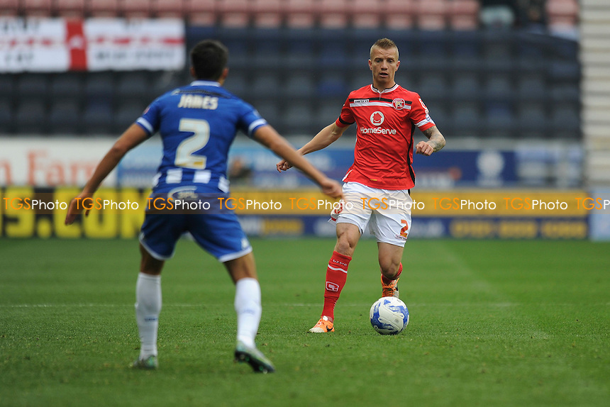 Jason Demetriou of Walsall holds up the ball from Reece James of Wigan Athletic during Wigan Athletic vs Walsall, Sky Bet League 1 Football at the DW Stadium, Wigan, England on 03/10/2015