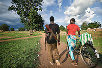 Young man with machine gun chatting to a girl with a bicycle in Tali Payam. Central Equatoria, South Sudan.