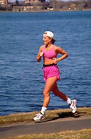 Adult woman age 26 jogging with tape around Lake Calhoun.  Minneapolis  Minnesota USA