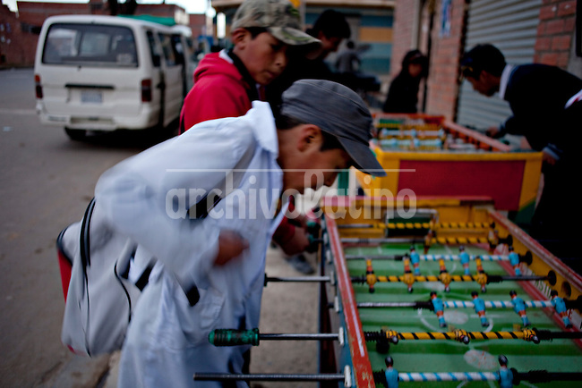 .School children playing table soccer.Just 25 years ago it was a small group of houses around La Paz  airport, at an altitude of 12,000 feet. Now El Alto city  has  nearly one million people, surpassing even the capital of Bolivia, and it is the city of Latin America that grew faster .<br /> 	It is also a paradigmatic city of the troubles  and traumas of the country. There got refugee thousands of miners that lost  their jobs in 90 ´s after the privatization and closure of many mines. The peasants expelled by the lack of land or low prices for their production. Also many who did not want to live in regions where coca  growers and the Army  faced with violence.<br /> 	In short, anyone who did not have anything at all and was looking for a place to survive ended up in El Alto.<br /> 	Today is an amazing city. Not only for its size. Also by showing how its inhabitants,the poorest of the poor in one of the poorest countries in Latin America, managed to get into society, to get some economic development, to replace their firs  cardboard houses with  new ones made with bricks ,  to trace its streets,  to raise their clubs, churches and schools for their children.<br /> 	Better or worse, some have managed to become a sort of middle class, a section of the society that sociologists call  emerging sectors. Many, maybe  most of them, remain for statistics as  poor. But clearly  all of them have the feeling they got  for their children a better life than the one they had to face themselves .