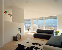 The light-filled open plan living room opens onto a balcony with a view of the surrounding mountains