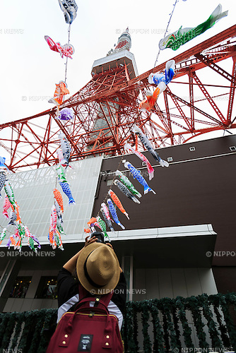 A man takes a picture of 333 Koinobori (carp-shaped windsocks or streamers) on display outside the Tokyo Tower to celebrate Childen's Day on May 2, 2016, Tokyo, Japan. Children's Day, formerly known as ''Boys Day,'' takes place annually on May 5 during the Golden Week holiday to celebrate healthy growth and well-being of children. It has been said that carp was chosen because of its strong and energetic nature, which are desirable traits for boys. (Photo by Rodrigo Reyes Marin/AFLO)
