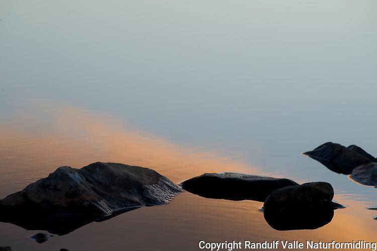 Farger fra solnedgang reflekteres i vannet. ---- Sunset reflecting in water.