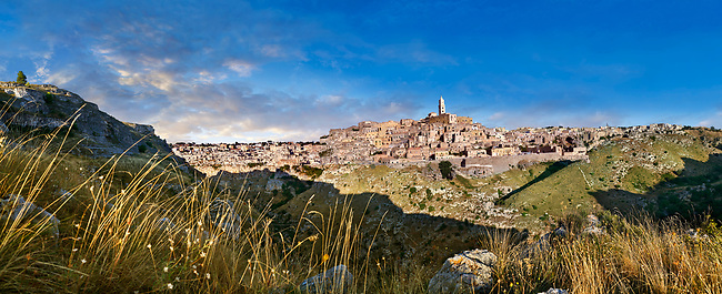 "Panoramic long view across ""la Gravina"" ravine to the Sassi of Matera at sunrise, Basilicata, Italy. A UNESCO World Heritage site.<br /> <br /> The area of Matera has been occupied since the Palaeolithic (10th millennium BC) making it one of the oldest continually inhabited settlements in the world. <br /> The town of Matera was founded by the Roman Lucius Caecilius Metellus in 251 BC and remained a Roman town until  was conquered by the Lombards In AD 664 becoming part of the Duchy of Benevento.  Matera was subject to the power struggles of southern Italy coming under the rule of the Byzantine Roman, the Germans and finally Matera was ruled by the Normans from 1043 until the Aragonese took possession in the 15th century. <br /> <br /> At the ancient heart of Matera are cave dwellings known as Sassi. As the fortunes of Matera failed the sassy became slum dwelling and the appalling living conditions became be the disgrace of Italy. From the 1970's families were forcibly removed from the Sassi and rehoused in the new town of Matera. Today tourism has regenerated Matera and the sassi have been modernised and are lived in again making them probably the longest inhabited houses in the world dating back 9000 years."