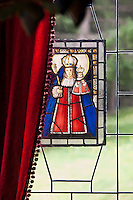 Detail of a stained glass window partly hidden by a red velvet curtain