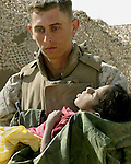AL ASAD, Iraq (June 8, 2005) -  A Marine from 2nd Marine Regiment, 3rd battalion, Lima Company carries a malnourished Iraqi boy, found in Dhulab, to the Regimental Aid Station to be treated. The Marines of 2d Marine Division conduct counter-insurgency operations with Iraqi Security Forces to isolate and neutralize Anti-Iraqi Forces, to support the continued development of Iraqi Security Forces, and to support Iraqi reconstruction and democratic elections in order to create a secure environment that enables Iraqi self-reliance and self-governance. (Official USMC photo by LCpl. Shane S. Keller)