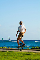 A man rides a unicycle on a path beside the ocean at Queens Beach in Waikiki.