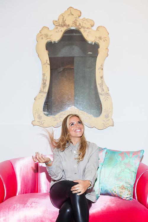 "Interior designer Sasha Bikoff at her new store in Tribeca on a vintage deco ""croissant"" sofa upholstered in pink velvet. <br /> <br /> <br /> Danny Ghitis for The New York Times"