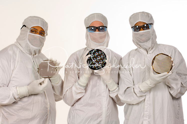 Employees of Tessera's Charlotte, NC, operations displays a sample of the digital optics applications the company produces via clean room manufacturing . The imaging and optics company makes wafer-level optics, image sensor packaging and ?smart? image enhancement technologies, and micro-optic solutions.