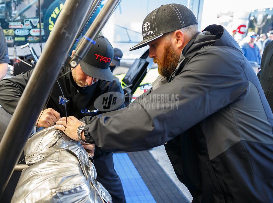 May 7, 2017; Commerce, GA, USA; NHRA top fuel driver Shawn Langdon (right) packs a parachute with the help of a crew member during the Southern Nationals at Atlanta Dragway. Mandatory Credit: Mark J. Rebilas-USA TODAY Sports