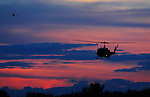 A Bell Huey helicopter shares the sunset sky over the Flagler County Airport with an Embry-Riddle Cessna 172, Thursday, Nov. 18, 2004.  With a helicopter consulting operation as well as a new flight school, operated by Embry Riddle Aeronautical University, now based at the rapidly growing facility, the skies are filling with aircraft.(Brian Myrick)