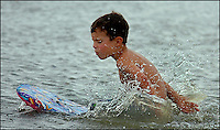 A young boy (model released) plays in the ocean on a summer day. Photo taken on Sullivan's Island, near Charleston, South Carolina beach on the Atlantic Ocean, but could represent a beach scene anywhere.