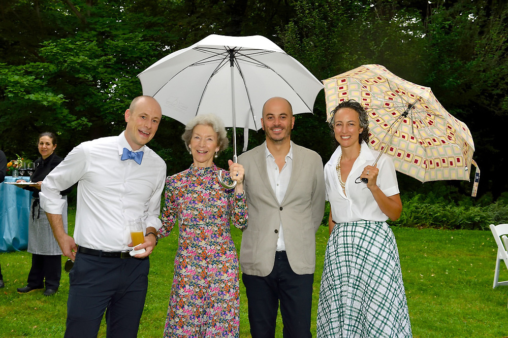 Guests posing for a photo on the lawn at a summer gala event.