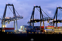 Twilight view of cranes loading a ship at a container terminal.