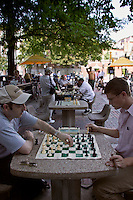People playing chess in Harvard Square on stone tables in plaza across from Harvard University, Cambridge, M
