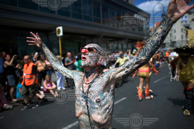 A man completely covered in tattoos marches during the Carnival of Cultures (Karneval der Kulturen) in Kreuzberg. The carnival celebrates Berlin's ethnic and cultural diversity.