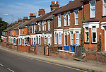 Row of old nineteenth century terraced red brick houses with bay windows, Ipswich, Suffolk, England