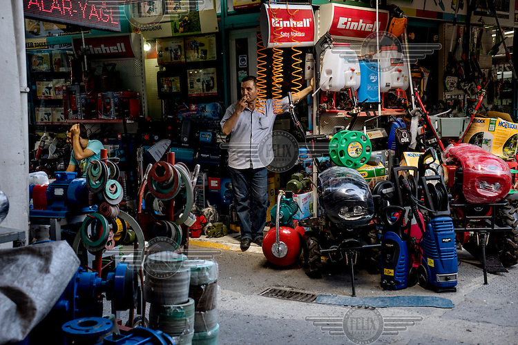 A man smokes a cigarette at the front of a hardware shop in Karakoy.