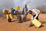 Adow Ibrahim Ali (right) provides water to Ibrahim Osman Mohammed in a remote section of eastern Kenya near the Somali border. Traveling with his cousin, the later man left his home in Buale, in the Middle Juba region of Somalia, three weeks before because a severe drought killed most of their animals. Their wives and children traveled ahead of them to the Dadaab refugee camp in vehicles, while they followed with the cart carrying their meager belongings. Already the world's world's largest refugee settlement, Dadaab has swelled in recent weeks with tens of thousands of recent arrivals fleeing drought in Somalia. The Lutheran World Federation, a member of the ACT Alliance, is manager of the camp, and in July opened a new extension to begin housing the newest refugees. Adow Ibrahim Ali is a leader in Dagahaley, one of three separate camps in the Dadaab complex. He also coordinates the ACT Alliance-sponsored Community Peace and Security Team in Dagahaley.