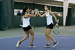 Alexis Franco (left) of the Wake Forest Demon Deacons slaps hands with double partner Eliza Omirou during their match against the Liberty Flames at the Wake Forest Indoor Tennis Center on March 11, 2017 in Winston-Salem, North Carolina. The Demon Deacons defeated the Flames 6-1.  (Brian Westerholt/Sports On Film)
