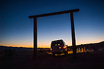 A vehicle (van) drives out the entrance gate at dusk, lower Sperry Wash