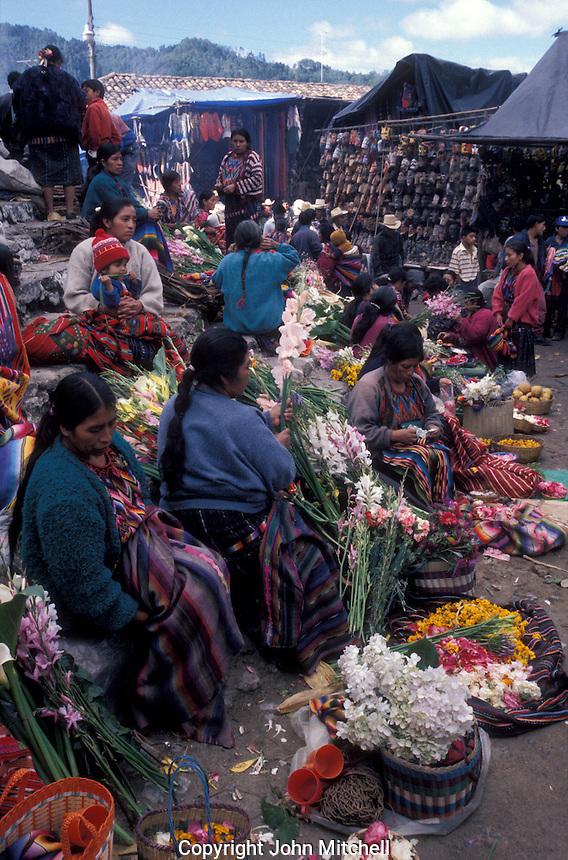 Quiche Maya women selling freshly cut flowers at the popular Sunday handicrafts market in Cichicastenango, Guatemala