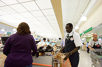 "John Madut (cq) steps in to bag groceries at the Toco Hills Publix on Friday, Sept. 1, 2006. One of the ""Lost Boys of Sudan,"" Madut has worked at the grocery store since 2003. This year he returned to Sudan for the first time since leaving and saw that his home town is in desperate need of clean drinking water. He's trying to help by raising funds for a new well, but has found the effort to be a financially monumental task."