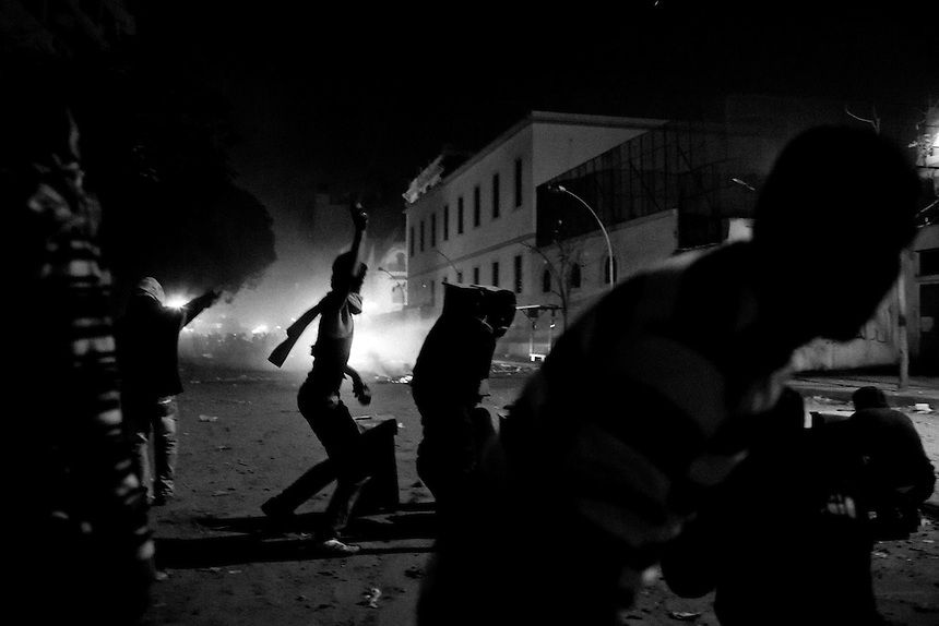 An Egyptian protester throws a stone toward a line of approaching riot police during clashes in downtown Cairo, February 3, 2012. Violent protests followed the deaths of over 70 football fans during a football match in the northern city of Port Said, as protesters tried to storm Egypt's Interior Ministry. Photo: Ed Giles
