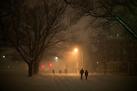People walk along an empty Memorial Drive in Cambridge, Massachusetts, USA, as Winter Storm Nemo approaches on Friday, Feb. 8, 2013.
