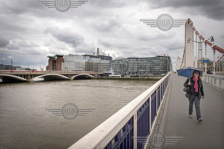 A woman crosses Chelsea Bridge with the Nine Elms development site and Battersea Power Station in the background.