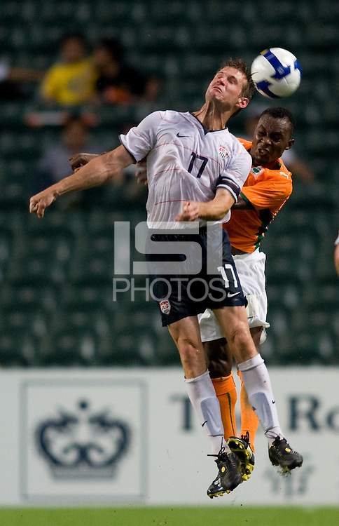 US captain (17) Brian McBride heads the ball with Ivory Coast defender (2) Serge Pascal Wawa during the game at Hong Kong Stadium.  The US Men's Olympic team tied Ivory Coast, 0-0, during the ING Cup in Hong Kong.
