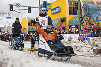 Katherine Keith and team leave the ceremonial start line with an Iditarider at 4th Avenue and D street in downtown Anchorage, Alaska during the 2015 Iditarod race. Photo by Jim Kohl/IditarodPhotos.com