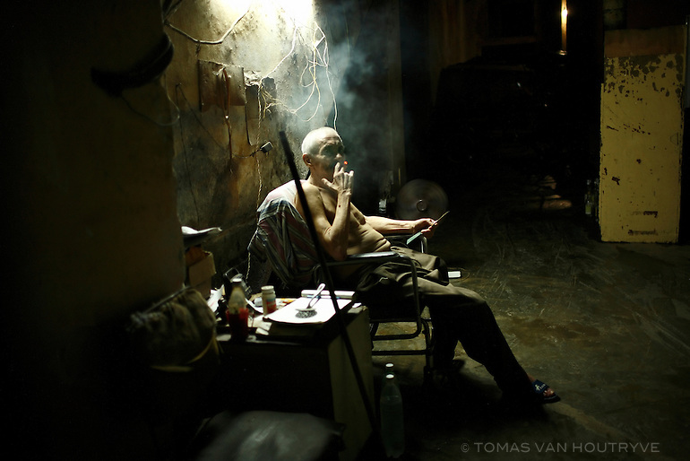 An elderly man smokes a cigar inside a garage in Old Havana, Cuba on 12 October 2008.