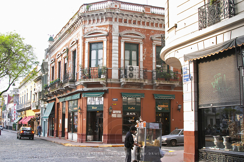 in the San Telmo district around Plaza Dorrego Square, a old houses around the square, all now housing antique shops., people walking on the street. Calle Defensa Defence street and Humberto, a street merchant selling popcorn from a mobile carriage Buenos Aires Argentina, South America