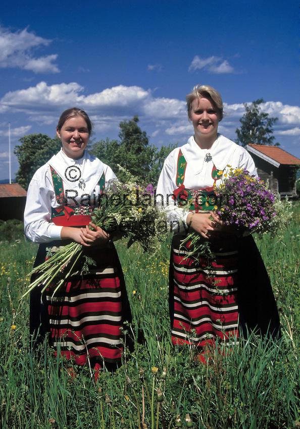 Sweden, Province Darlana, young women gathering flowers for midsummer celebration   Schweden, Provinz Darlana, einhimische, junge Frauen in Landestracht sammeln Wiesenblumen fuer das Mittsommerfest