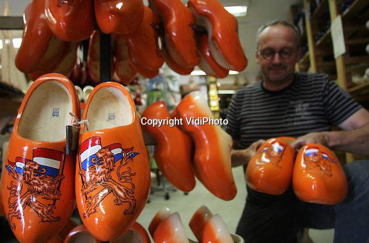 Foto: VidiPhoto..HEINKENSZAND - Klompenmakerij Traas uit het Zeeuwse Heinkenszand bereidt zich alvast voor op de voetbalgekte rond het Nederlands elftal nu het team officieel het beste ter wereld is en het EK er zit aan te komen. Het bedrijf is volop bezig met de productie van oranje klompen. Bovendien is de houten schoen helemaal terug van weggeweest. Het oer-Hollandse product blijkt enorm in populariteit toe te nemen bij tuinliefhebbers.Traas verwacht dit jaar driemaal zoveel klompen om te zetten dan vorig jaar. Het Zeeuwse klompenfabriekje is één van de acht nog overgebleven commerciële klompenmakers van ons land. Zo'n 20 procent van de klompen gaat naar boeren en stratenmakers. De rest is voor 'fundragers', tuinliefhebbers en bedrijven die de klomp laten bedrukken met hun logo als relatiegeschenk.