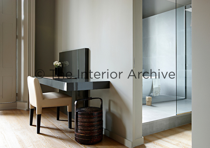 A partition wall separates a bedroom area from an en-suite bathroom. A custom made polished black desk stands on one side with an upholstered chair.