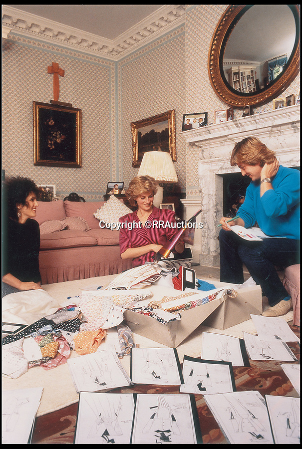 BNPS.co.uk (01202 558833)<br /> Pic: RRAuctions/BNPS<br /> <br /> Princess Diana with David and Elizabeth Emanuel, looking through outfit designs for her visit to Saudi Arabia.<br /> <br /> Fascinating sketches of outfits designed for Princess Diana's visit to Saudi Arabia 32 years ago have come to light - and they include a burka.<br /> <br /> Before Diana and Prince Charles embarked on their 1986 tour of the Gulf states, one of her favourite designers was contacted by Diana's lady in waiting with instructions to make dresses which 'conformed to local customs'.<br /> <br /> The husband and wife team David and Elizabeth Emanuel, who made Diana's wedding dress, submitted sketches for four different demure, long sleeved outfits.<br /> <br /> The fifth, 'reserve' outfit, which was also sketched, was a burka covering Diana from head to toe with only a gap for her eyes.