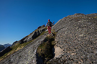 Female hiker descends rocky ridge towards Nonstind mountain peak, Moskenesøy, Lofoten Islands, Norway