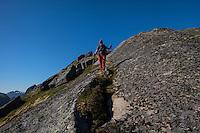 Female hiker descends rocky ridge towards Nonstind mountain peak, Moskenesøy, Lofoten Islands, Norway