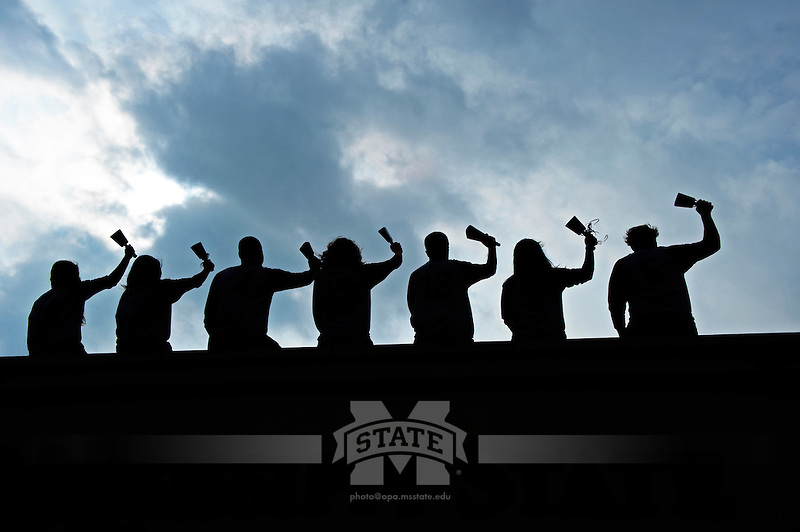 Silhouette of students ringing cowbells (photo by Beth Wynn / © Mississippi State University)
