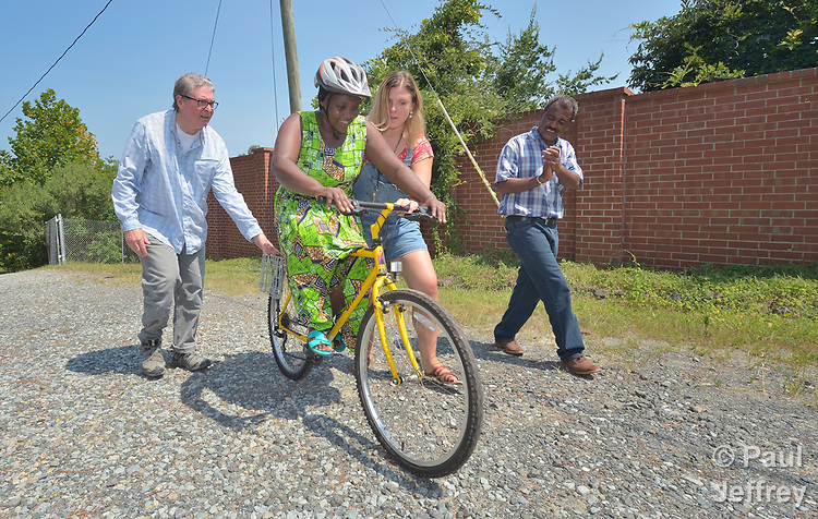 Evanis Gatunzi, a refugee from Rwanda, rides a bike for the first time in Durham, North Carolina, on July 22, 2017. She&rsquo;s helped by Greg Garneau, a volunteer who coordinates the refugee bike program for the Durham Bicycle Co-op, and Monique Lohmeyer, a case manager for Church World Service. In the background, Yosef Birhane, a refugee from Eritrea, cheers her on.<br /> <br /> Church World Service resettles refugees in North Carolina and throughout the United States.<br /> <br /> Photo by Paul Jeffrey for Church World Service.