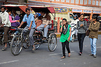 Jaipur, Rajasthan, India.  Street Traffic; Women Crossing the Street, Passengers Riding Rickshaws.