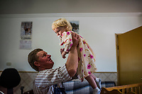 CAPULIN, MEXICO - OCTOBER 31: The Mexican Mennonite Johan Giesbrecht lifts his daughter out of her crib during lunch on the 31st of October, 2015 in Capulin, Mexico. <br /> <br /> Daniel Berehulak for The New York Times