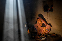 INDIA, Madhya Pradesh , woman cooks with firewood in clay hut, preparing Chapathis, the indian bread, the toxic fume may cause lung diseases