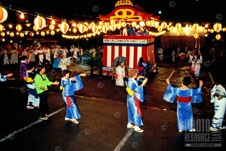 Bon dancers in various poses circle around a shrine strung with hundreds of lanterns in Nuuanu on the island of Oahu.
