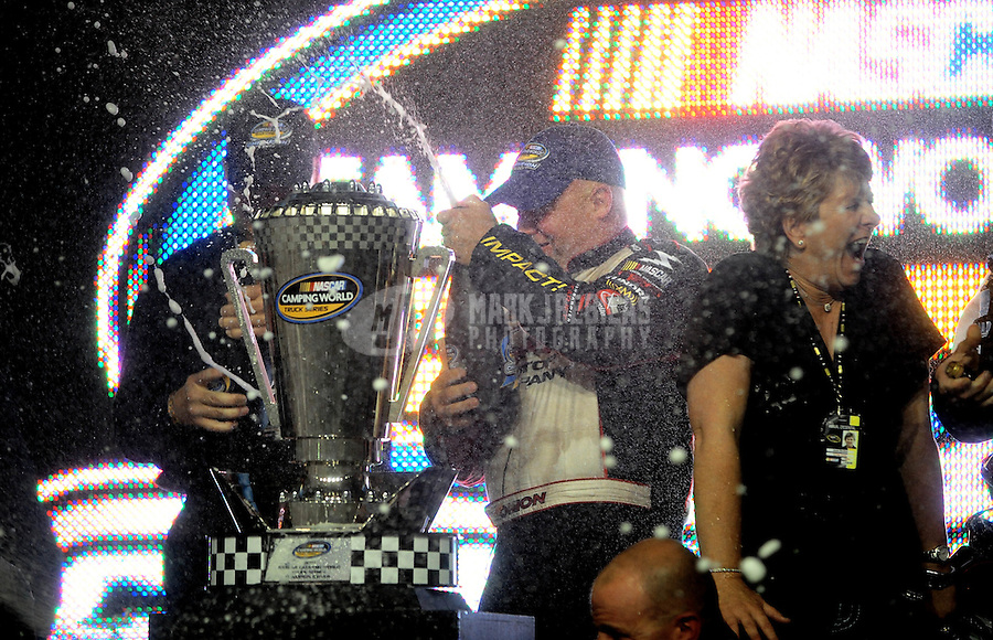 Nov. 19, 2010; Homestead, FL, USA; NASCAR Camping World Truck Series driver Todd Bodine (center) celebrates with champagne alongside wife Janet Bodine as the 2010 series champion following the Ford 200 at Homestead Miami Speedway. Mandatory Credit: Mark J. Rebilas-