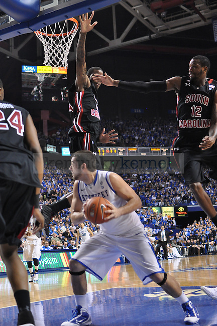 UK's Josh Harrellson is stopped by two South Carolina defenders as he attempts to go up for his shot.