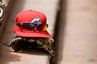 A Columbus Clippers cap sits on top of a glove in the visitors dugout at Knights Stadium May 25, 2010, in Fort Mill, South Carolina.  Photo by Brian Westerholt / Four Seam Images